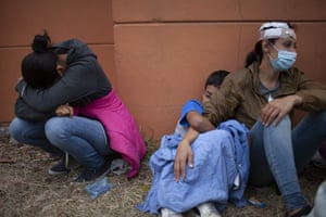 Injured women, part of the Honduran migrant caravan, are distraught as they sit on the side of a highway after clashing with Guatemalan police and soldiers in Vado Hondo.