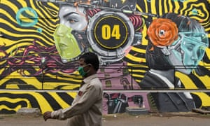 A man wearing a mask walks past a graffiti raising awareness on wearing of face masks to prevent the spread of the coronavirus in Mumbai.