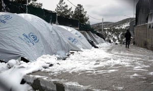 A migrant walks next to snow-covered tents in Lesbos.