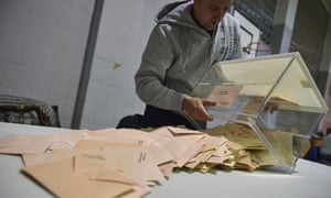 An election official empties a ballot box to count votes at a polling station for Spain's general election in Pamplona, Spain, Sunday, April 28, 2019.