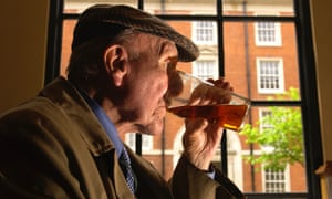 An old man drinking a pint of beer in a pub