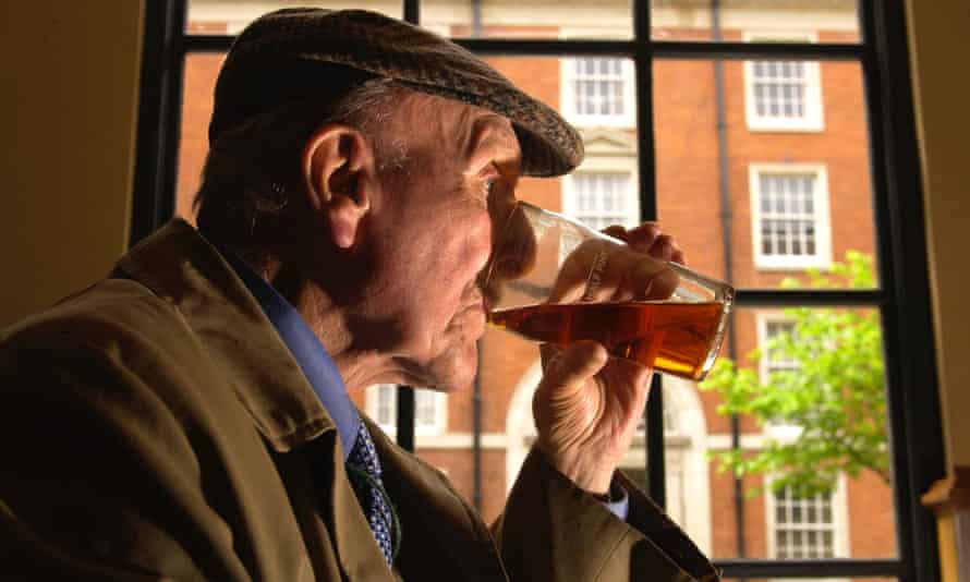 A man drinking a pint of beer in a pub