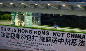 An activist ties a banner that reads 'This is Hong Kong, not China' to a pedestrian bridge leading to the Legislative Council in Hong Kong