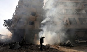 A man walks in front of a burning building after a Syrian air force strike in Damascus.