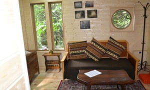Interior of one of the forest treehouses showing a sofa and table. Family adventure break destination near Les Chambres, France.