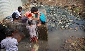 children at a water pipeline surrounded by sewage in Mumbai