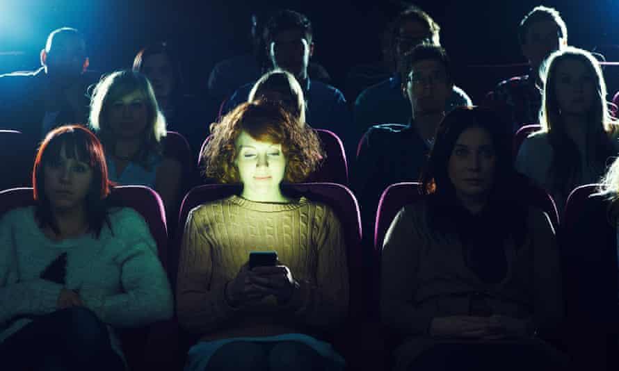 Woman using mobile phone in cinema