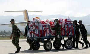 Troops unload aid supplies at Palu airport as international help began to arrive in Sulawesi.