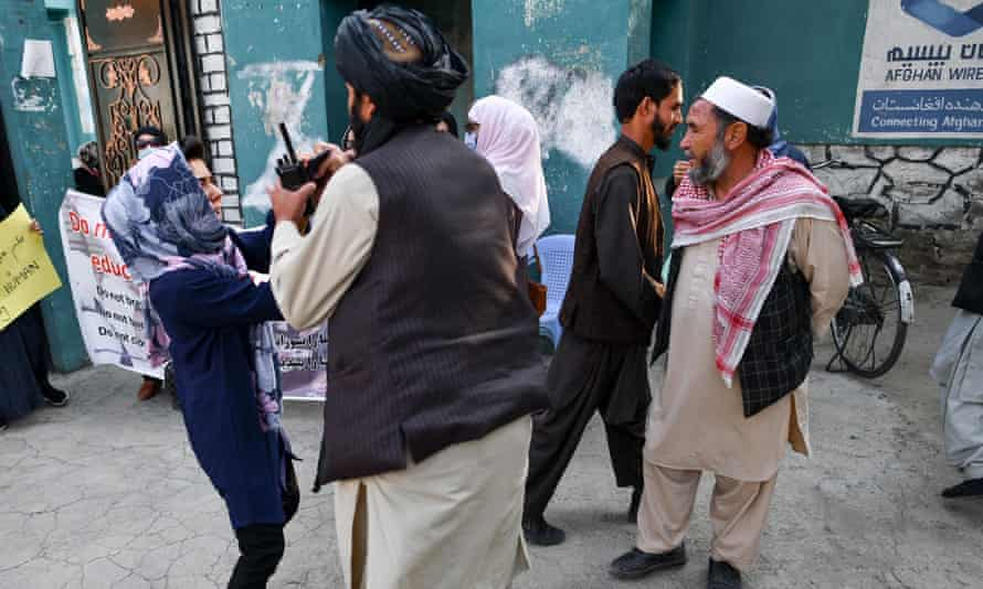 A female protestor scuffles with a member of the Taliban during a demonstration outside a school in Kabul on 30 September