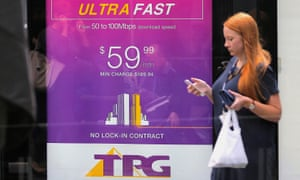 A woman walks past an ad for TPG