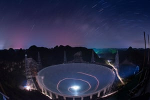 Pingtang county, China. A vehicle leaves light trails in a long exposure photograph as it drives beneath the 500-metre Aperture Spherical Radio Telescope. Construction on the device began in 2011 and is nearing completion