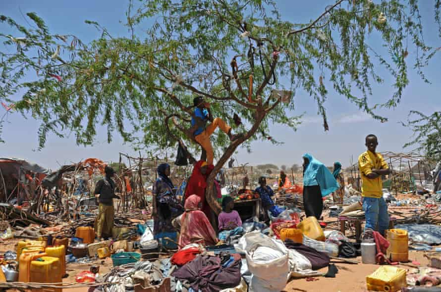 Somali refugees displaced by conflict wait with their belongings after soldiers destroyed their temporary shelters.