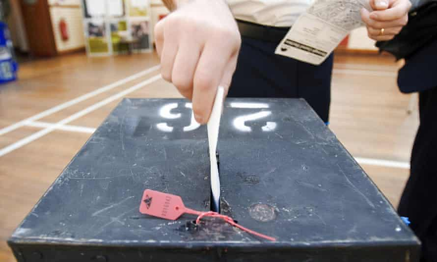 A voter places his voting card into a ballot box at a polling station.