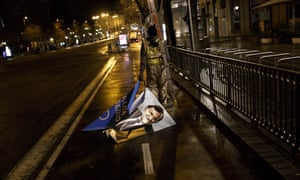 A campaign poster depicting Spain's prime minister, Mariano Rajoy, is removed.