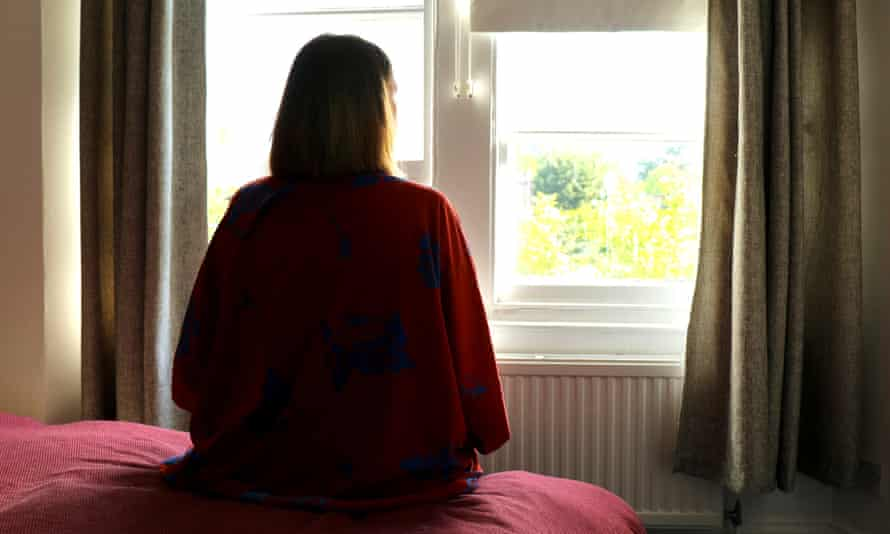 Lone woman sitting on the bed looking out of the window during coronavirus lockdown.