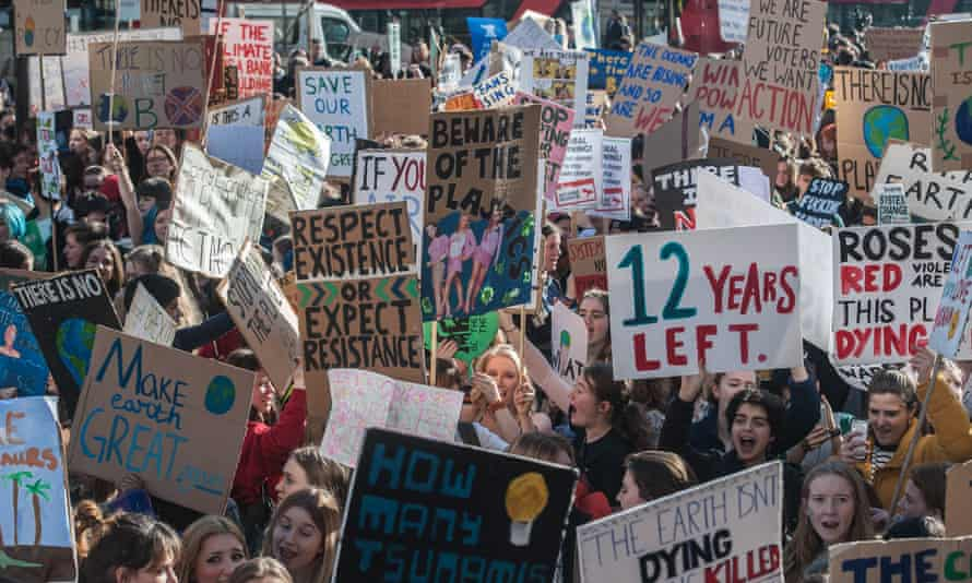 a huge crowd of striking children holding up protest banners.