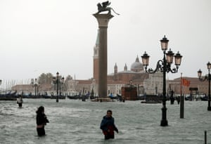 People walk in flooded Saint Mark Square during a period of seasonal high water in Venice, Italy