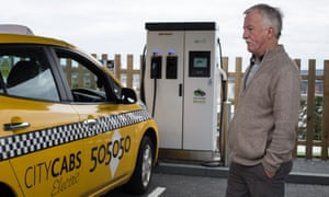 James Leaburn admires his electric taxi during a charging stop at the Princes Street charging station.