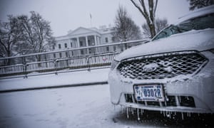 A police car next to the White House is covered as snow falls in Washington.