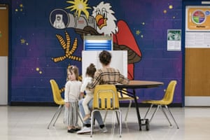 A woman with her two young daughters marks down her vote at a polling place in Armstrong elementary school
