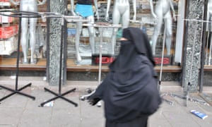 A woman in a burqa walks past shops in London.