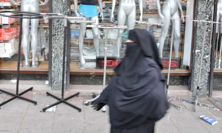 A woman in a burqa walks past shops in London.