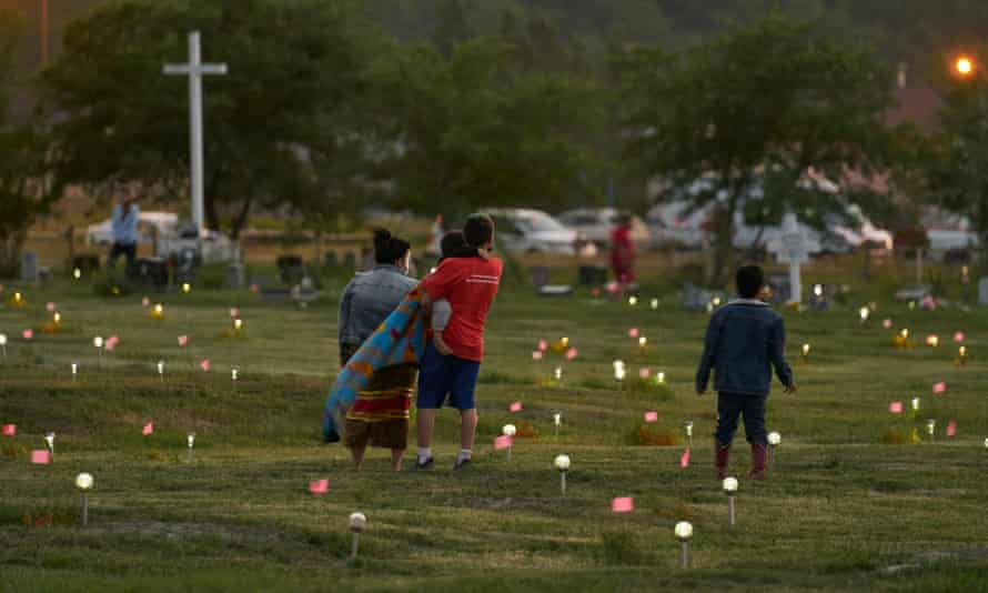 A family walks through a field on 26 June where flags and solar lights mark the site where human remains were discovered in unmarked graves at the former Marieval Indian residential school site.