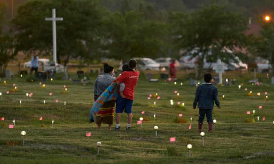 A family walks through a field where flags and solar lights now mark the site where more than 750 unmarked graves were discovered at the former Marieval Indian school in Saskatchewan on 26 June.