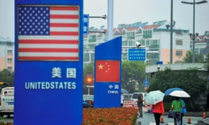 Signs with the US flag and Chinese flag are seen outside a store in Qingdao in China's eastern Shandong province. President Trump said on Thursday it was unlikely he would meet China's President Xi Jinping before US tariffs are imposed on Chinese imports