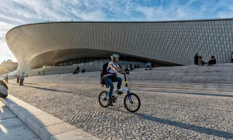 Cyclist passes the MAAT - Museum of Art, Architecture and Technology, Lisbon