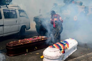 Coffins of two the dead are dropped as tear gas engulfs the procession.