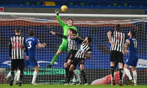 Kepa Arrizabalaga of Chelsea punches the ball clear under pressure from Ciaran Clark and Jamaal Lascelles of Newcastle United.