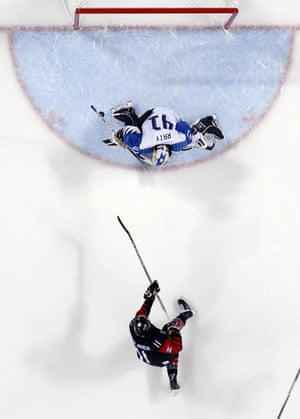 Cananda's Jillian Saulnier scores against past goalie Finland's during the second period of the preliminary round of the women's ice hockey.