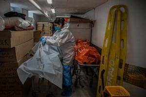 A funeral worker handles coronavirus victims, New York.