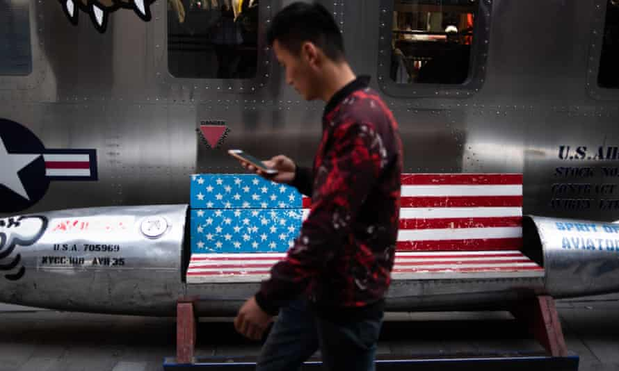 A man walks by a bench featuring a US flag outside a store in Beijing, China.