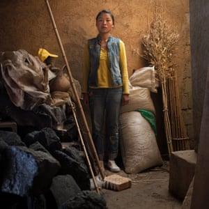 Xundian, China. Wang Zhi Hui, a tobacco grower, in her family's barn