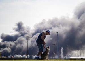 Texas, USA man walks his dog while smoke billows in the background after an explosion at a chemical plant in Port Neches. Multiple workers were injured in a massive blast that also blew out windows and doors of nearby homes.