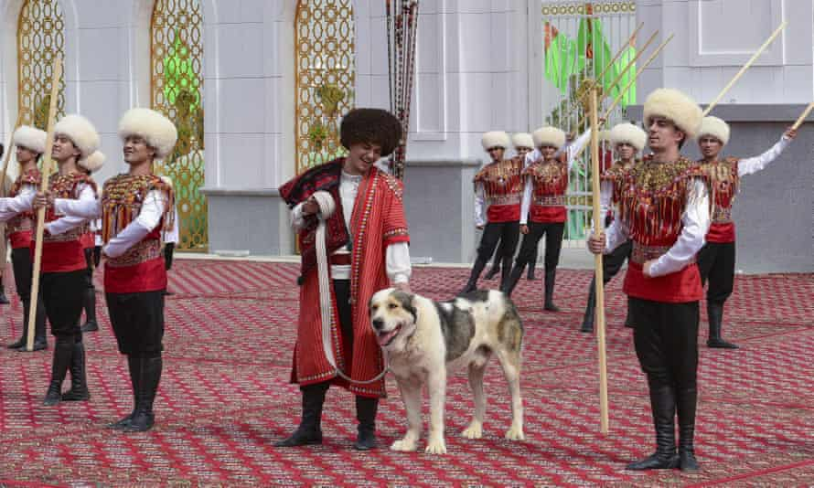 A man dressed in a national costume pets his border guard shepherd dog Alabai during the Dog Day celebration in Ashgabat