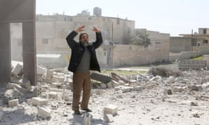 A man gestures in the ruins of a building after an air strike allegedly by pro-Assad forces in the Syrian village of Sarmin, Idlib province