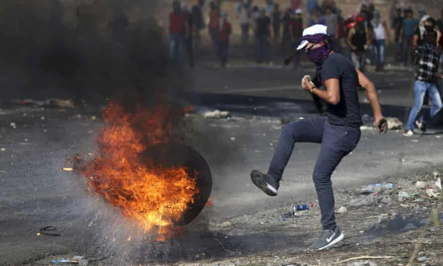 Palestinian protester kicks a burning tyre during clashes with Israeli troops near Nablus.