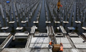 Workers construct a new pier at New Priok container terminal in north Jakarta, Indonesia