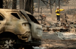 Firefighters search through a burned residence during the Bear fire in the Berry Creek area of unincorporated Butte county, California, on 14 September.