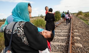 A Syrian woman holds her child while she rests on the railway line used as a crossing point into Hungary