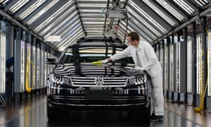 A worker at Volkswagen's factory in Dresden prepares a car for delivery.