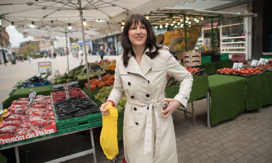 woman in a beige raincoat in front of some market stalls