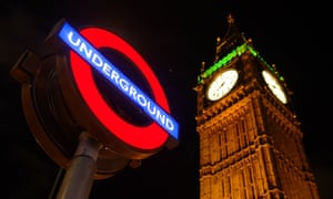 Jubilee Tower (Big Ben) at night, with the London Underground sign lit up in the foreground