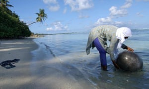 A villager washes a cooking pot in the sea around Huraa island, Maldives. The Green Climate Fund is allocating $23.6m to fight water shortages in the low lying atolls.