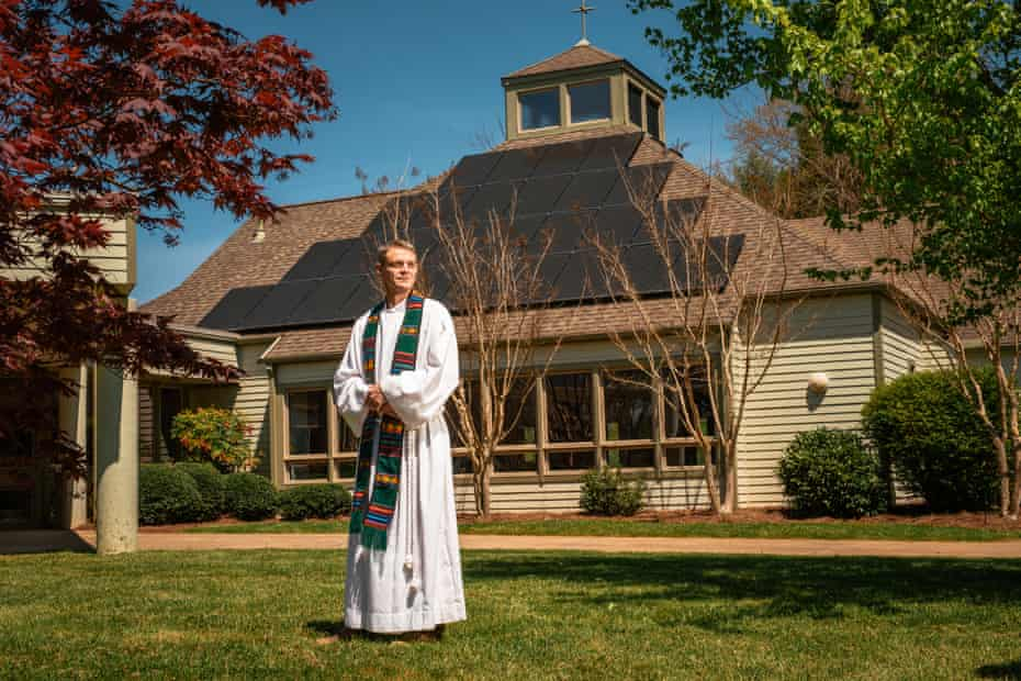 The Rev Scott Hardin-Nieri in front of the solar panels at the First Christian church in Black Mountain, North Carolina.