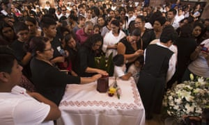 Relatives of Jose Alfredo López Guillén touch an urn that contains his ashes during a memorial mass.