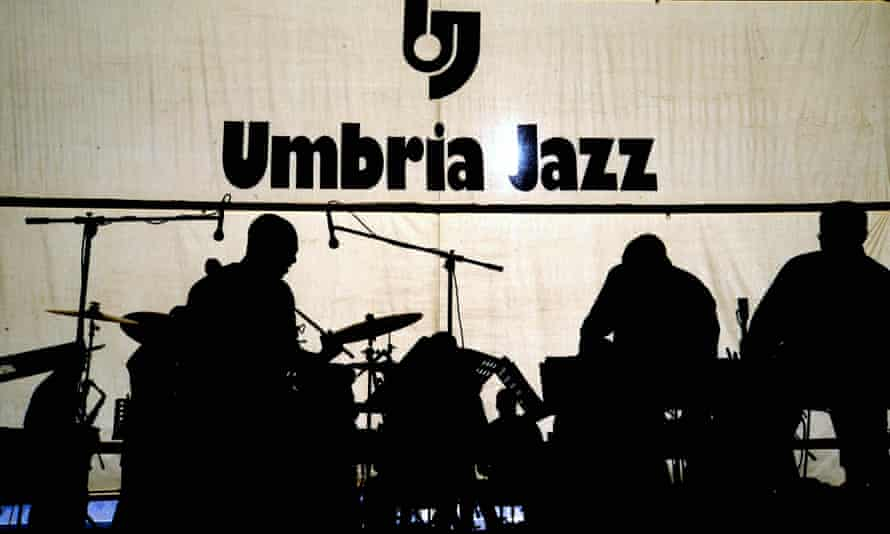 Silhouette of three musicians against a backdrop reading Umbria Jazz, at the Umbria Jazz Festival in Perugia, Italy
